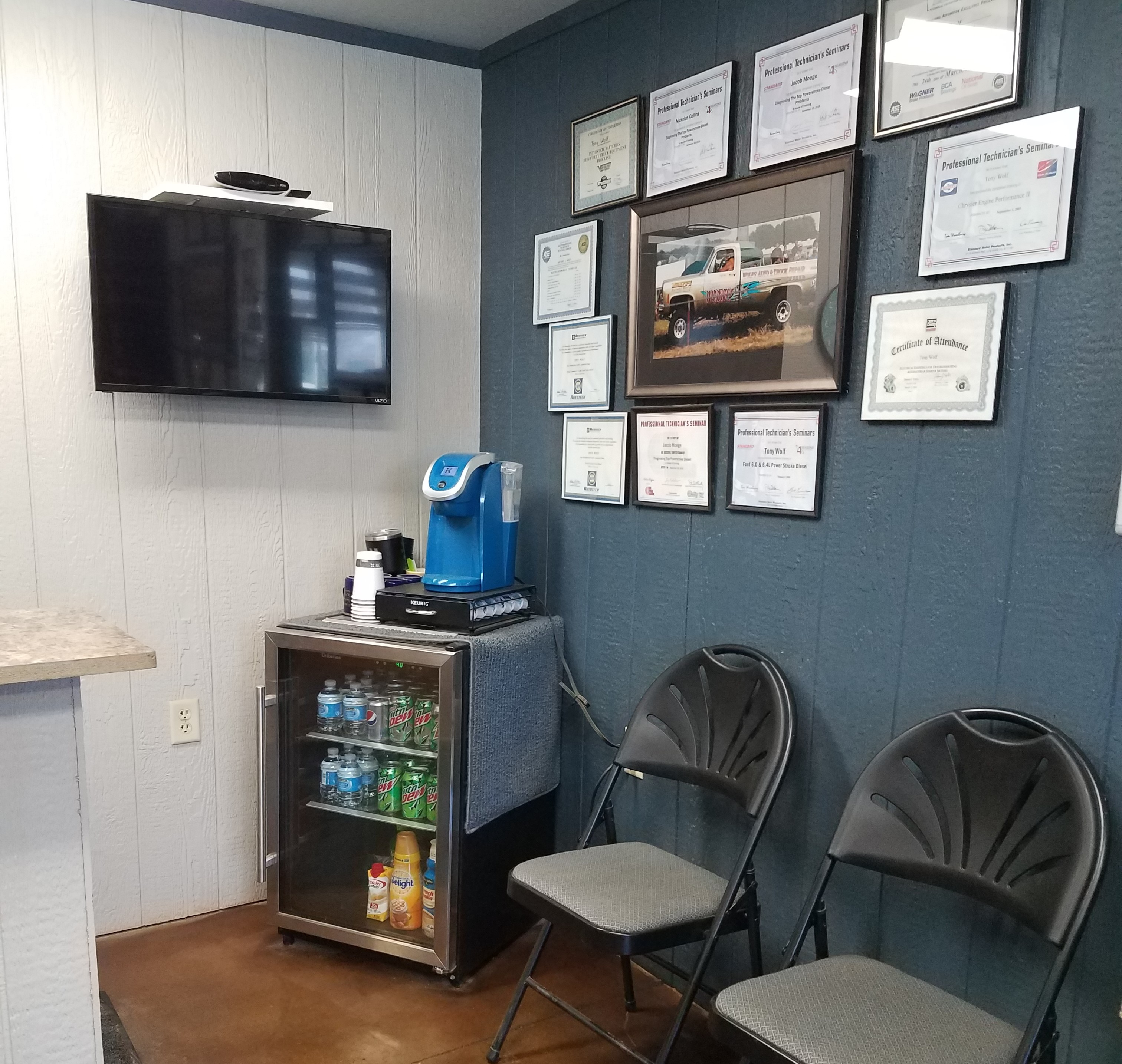 interior view of the waiting room in Wolf's Auto and Truck Repair with chairs, fridge, and a tv
