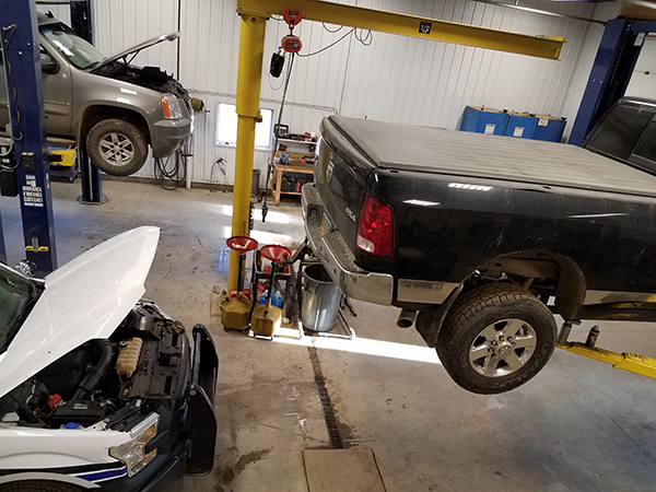 a black truck on a lift being worked on in the shop in wolf's auto and truck repair shop