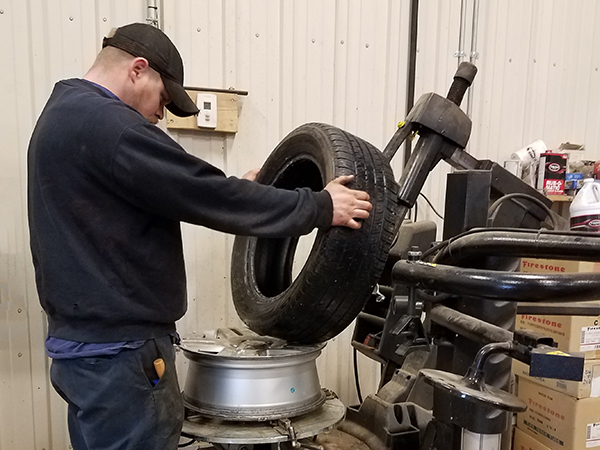 a mechanic inspecting a tire at wolf's auto and truck repair